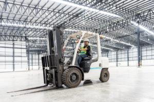 Warehouse worker driver in uniform at storage warehouse