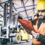 Worker in protective uniform in front of forklift